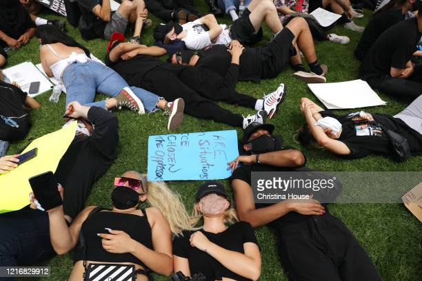 Demonstrators lay down to approximate the time that George Floyd was on the ground during a peaceful protest outside the Cerritos Sheriff's Station...