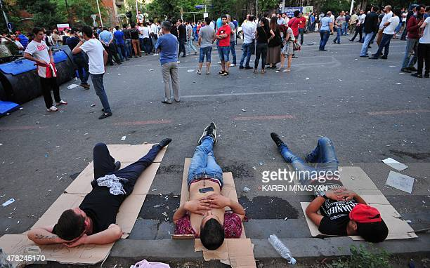 Demonstrators lay on a street during a protest against an increase of electricity prices in the Armenian capital Yerevan on June 24 2015 Hundreds of...
