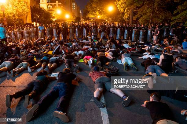 TOPSHOT Demonstrators lay on the ground facing a police line in front of the White House during protests over the death of George Floyd on June 3 in...