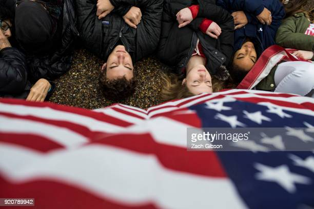 Demonstrators lie on the ground during a 'liein' demonstration supporting gun control reform near the White House on February 19 2018 in Washington...