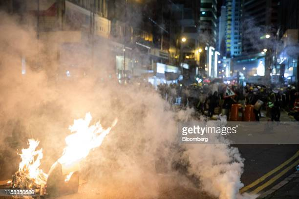 Demonstrators light a fire in the middle of the road during a protest in the Sheung Wan area of Hong Kong, Chin, on Sunday, July 28. From an airport...