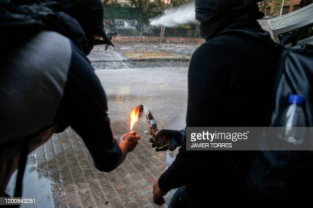Demonstrators light a molotov cocktail during a protest against the government of President Sebastian Pinera in Santiago on February 14 2020...