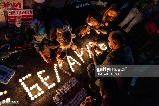 Demonstrators light candles and form a word Belarus outside the Belarusian embassy during a protest against the results of Belarusian presidential...