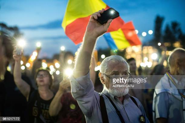 Demonstrators light their phone lights as they gather in front of the Romanian Prime Minister's office building on June 21 2018 in Bucharest Romania...