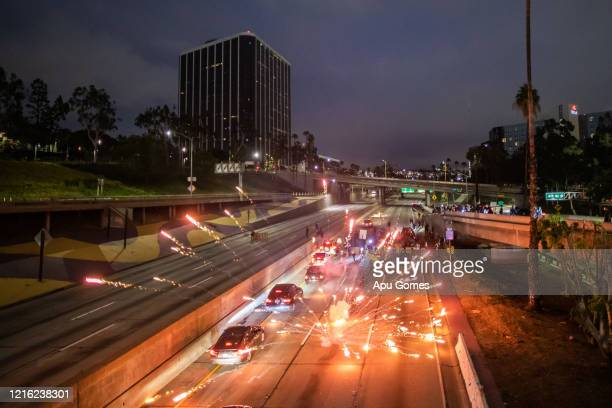 Demonstrators lights fireworks while they shut down the Freeway 110 North in downtown Los Angeles response to the police killing of George Floyd on...