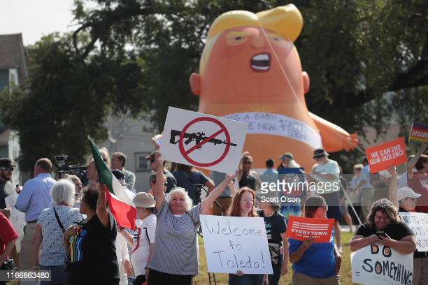 Demonstrators line the street near the Miami Valley Hospital in anticipation of a visit from President Donald Trump on August 07, 2019 in Dayton,...