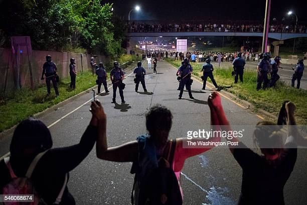 Demonstrators link arms as they block I-94 near the Dale St. Exit during a protest for Philando Castile in Falcon Heights, Minn. On Saturday July 09,...