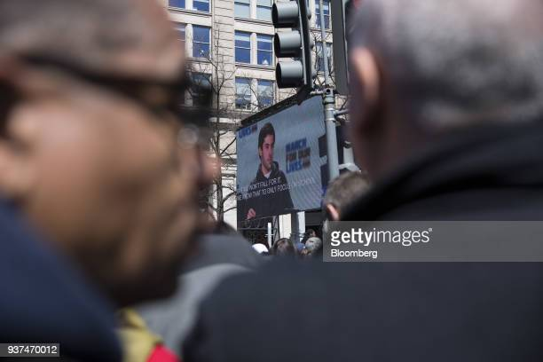 Demonstrators listen as a speaker is displayed on a monitor on Pennsylvania Avenue during the March For Our Lives in Washington DC US on Saturday...