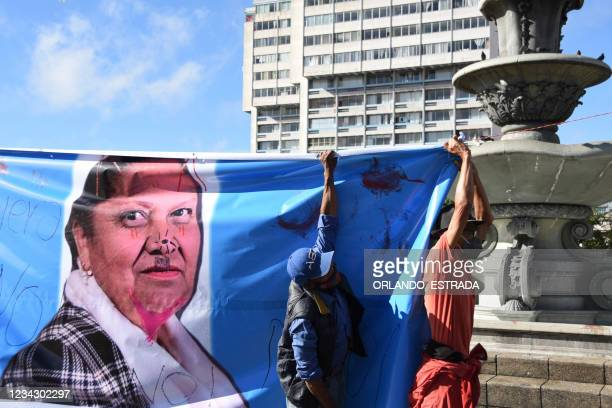 Demonstrators load a banner with a vandalised photograph of Guatemala's Attorney General Consuelo Porras during a protest demanding the resignation...