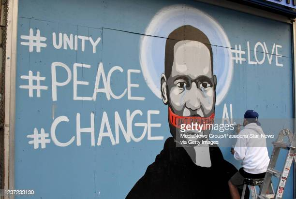 Demonstrators look on as artist Celos paints a mural of George Floyd along Broadway after the death of George Floyd a black man who was in police...