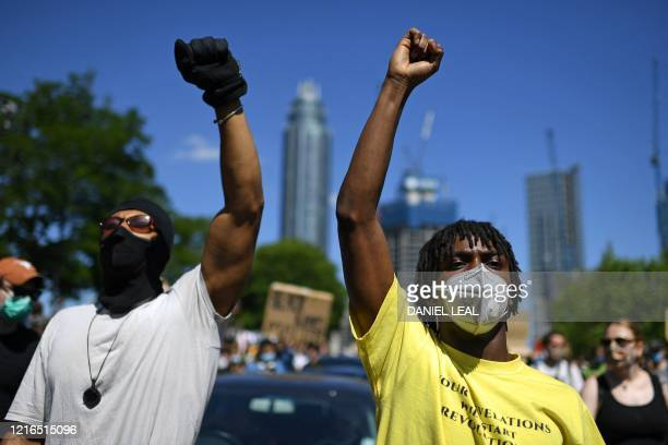 Demonstrators make black power salutes as they make their way towards the US Embassy in central London on May 31 2020 to protest the death of George...