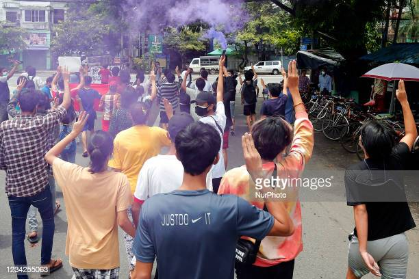 Demonstrators make the defiant three-finger salute and hold flares as they march during a flash mob protest against the military coup in Yangon,...