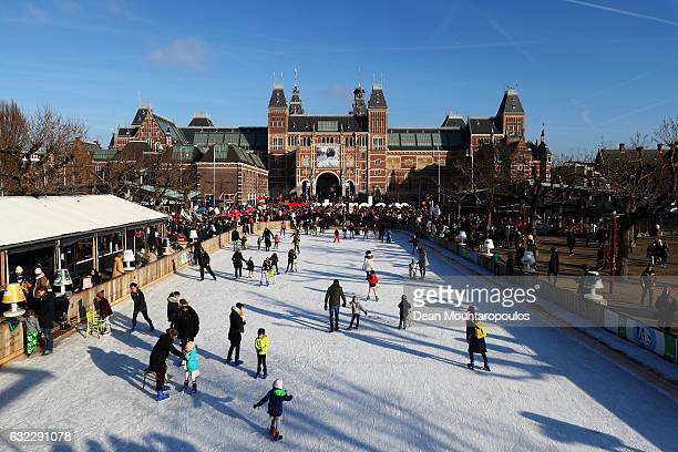 Demonstrators make their way from the iamsterdam statue in front of the Rijksmuseum towards US Consulate as skaters on the temporary Ice Rink skate...