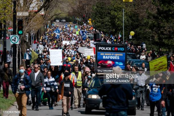 Demonstrators march against new Covid-19 anti-mask and anti-curfew restrictions, in Montreal on May 1, 2021. - The new restrictions issues by the...