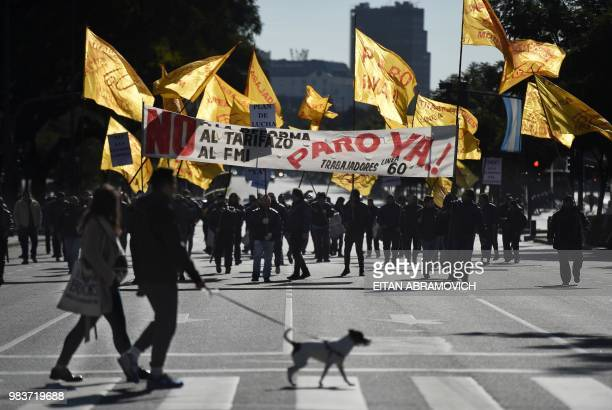 Demonstrators march along 9 de Julio avenue in Buenos Aires on June 25 during a 24hour general strike called by Argentina's unions in protest of the...
