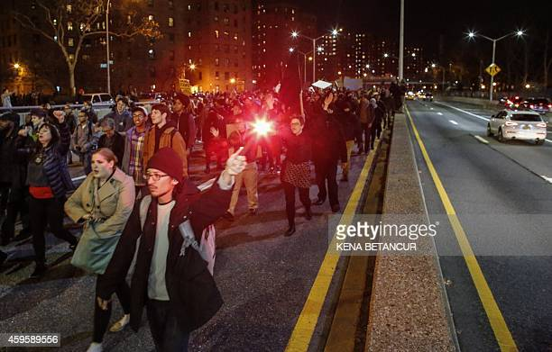 Demonstrators march along FDR drive during a protest November 25 2015 in New York City one day after a grand jury decision not to prosecute a white...