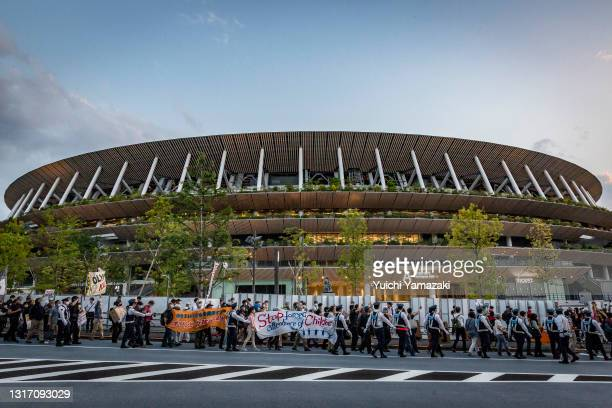 Demonstrators march around the New National Stadium, the main stadium for the Tokyo Olympics, during a protest against the Tokyo Olympics on May 09,...