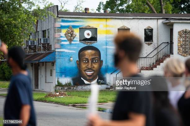 Demonstrators march by a mural of Ahmaud Arbery after a court appearance by Gregory and Travis McMichael, two suspects in the fatal shooting of...