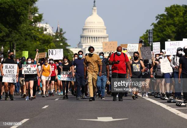 Demonstrators march down Pennsylvania Avenue near the Trump International Hotel during a protest against police brutality and the death of George...