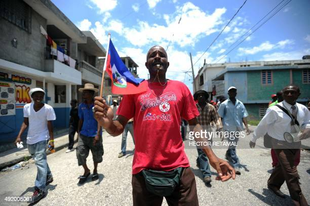 Demonstrators march during a protest against the government of President Michel Martelly during Haitian Flag Day in PortauPrince on May 18 2014...