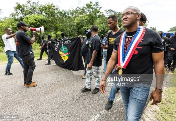 Demonstrators march during a protest over security and the state of the economy near Kourou space center on April 4 2017 in Kourou French Guiana The...
