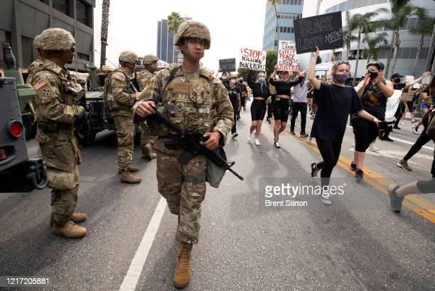 Demonstrators march near the National Guard in response to George Floyd's death on June 2 2020 in Los Angeles California Floyd died while in...