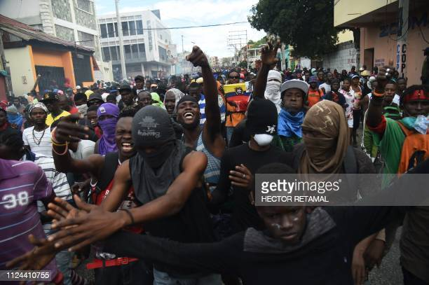 TOPSHOT Demonstrators march on the streets during demonstration in the centre of Haitian Capital PortauPrince February 12 on the sixth day of protest...