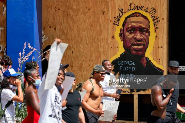 Demonstrators march past a mural remembering George Floyd during a peaceful protest against police brutality and racism on June 6 2020 in Dallas...