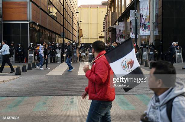 Demonstrators march past police officers in riot gear during a protest against the gasoline price hike in Mexico City Mexico on Monday Jan 9 2017 The...