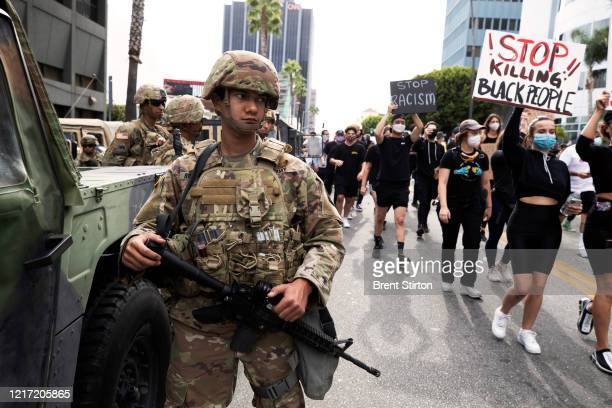 Demonstrators march past the National Guard in response to George Floyd's death on June 2 2020 in Los Angeles California Floyd died while in...