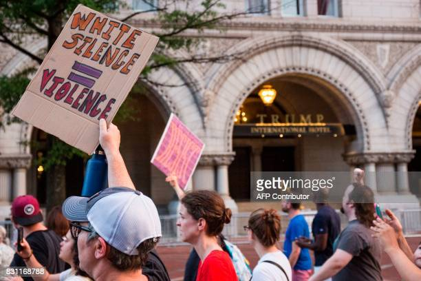 Demonstrators march past the Trump International Hotel August 13 2017 in Washington DC en route to a statue of Confederate General Albert Pike the...