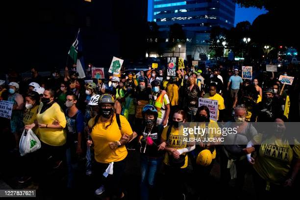 Demonstrators march to the Justice Center during a night of protest against police brutality and the deployment of federal troops to US cities on...