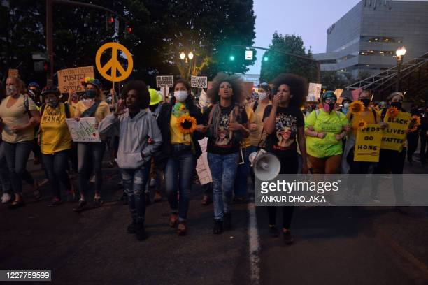 Demonstrators march to the Multnomah County Justice Center in Portland, Oregon, on July 23, 2020. - Police fired teargas and fought running battles...