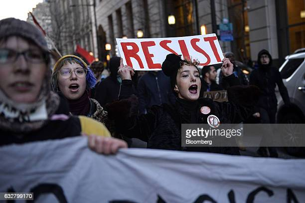 Demonstrators march while chanting and carrying placards and banners during a protest outside the Republican Party's annual policy retreat in...