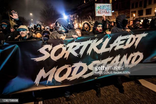 Demonstrators march with a banner reading 'Black-clad resistance' during a protest march organised by radical group 'Men in Black Denmark' against...