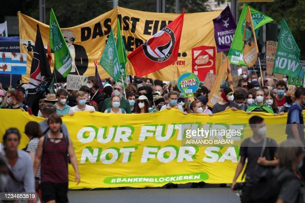 Demonstrators march with a banner reading 'Our future is not for sale' in front of the Deutsche Bank headquarters during a demonstration called by...