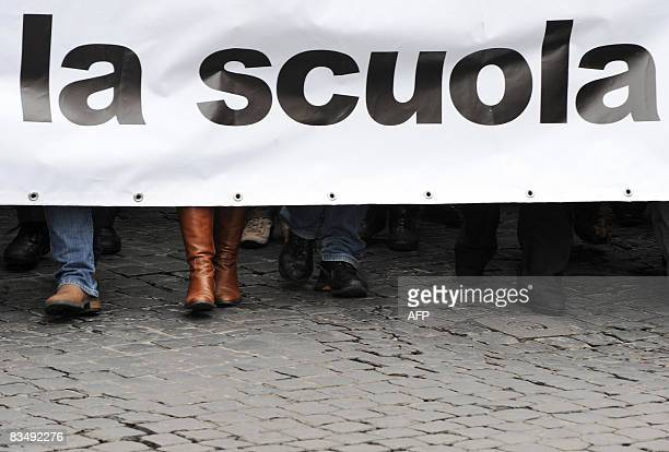 Demonstrators march with a banner reading 'The school' as hundreds of thousands of teachers students and parents demonstrated in Rome on October 30...
