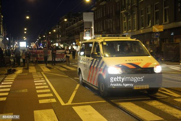 Demonstrators march with a police vehicle escorting them during a protest called by the Dutch Antifascist Action AFA against the violence that took...