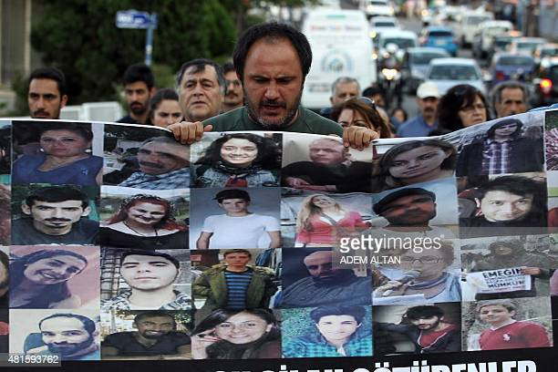 Demonstrators march with a poster showing the faces of victims killed in a suicide bomb attack in the southern Turkish town of Suruc two days before...