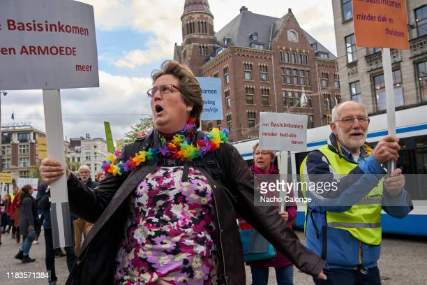 Demonstrators march with placards during the basic income demonstration on October 26 2019 in Amsterdam Netherlands The protesters called for a basic...