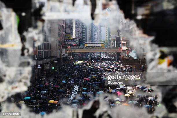 Demonstrators marching along Hennessy Road are seen through a ripped poster displayed on a bridge during a protest in the Causeway Bay district of...