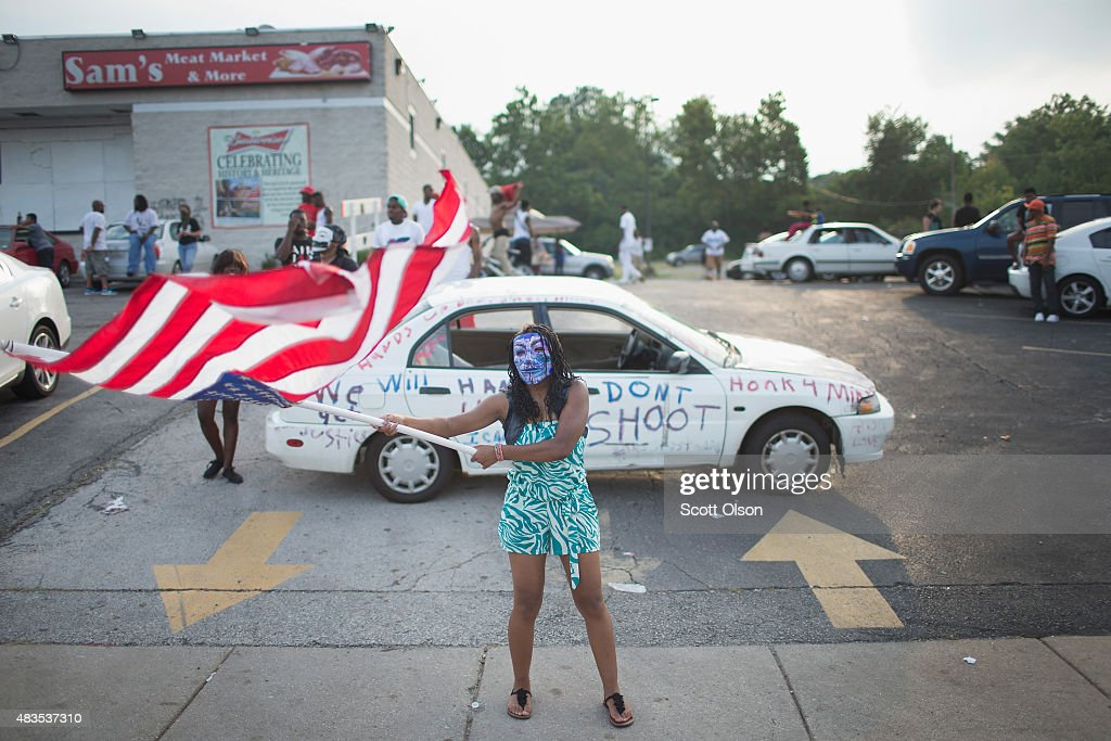 Demonstrators, marking the one-year anniversary of the shooting of Michael Brown, protest along West Florrisant Street on August 9, 2015 in Ferguson, Missouri. There are reports that two people were shot when gun fire broke out during protests later in the evening. Brown was shot and killed by a Ferguson police officer on August 9, 2014. His death sparked months of sometimes violent protests in Ferguson and drew nationwide focus on police treatment of black suspects.