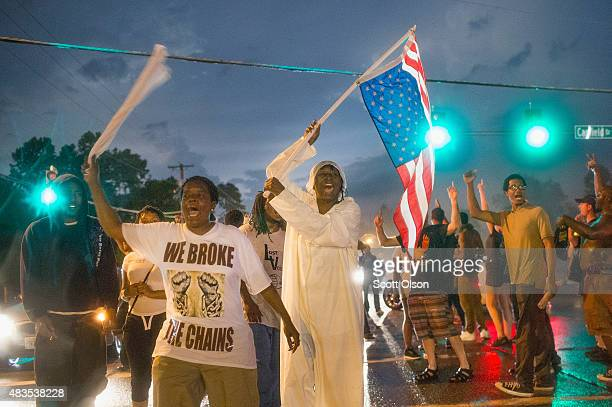 Demonstrators marking the oneyear anniversary of the shooting of Michael Brown march along West Florrisant Street on August 9 2015 in Ferguson...