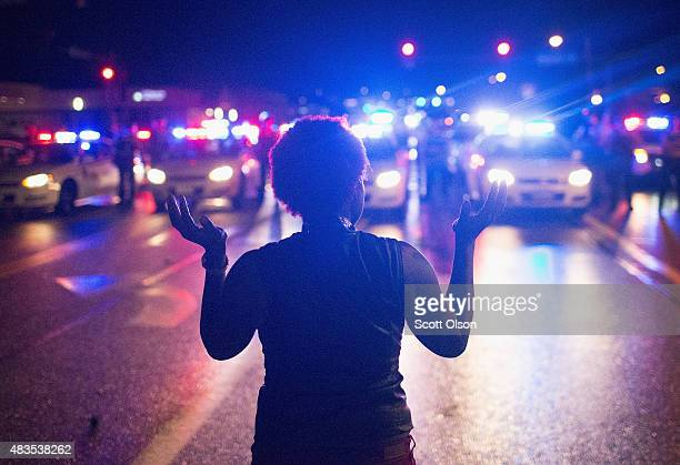 Demonstrators marking the oneyear anniversary of the shooting of Michael Brown face off with police during a protest along West Florrisant Street on...