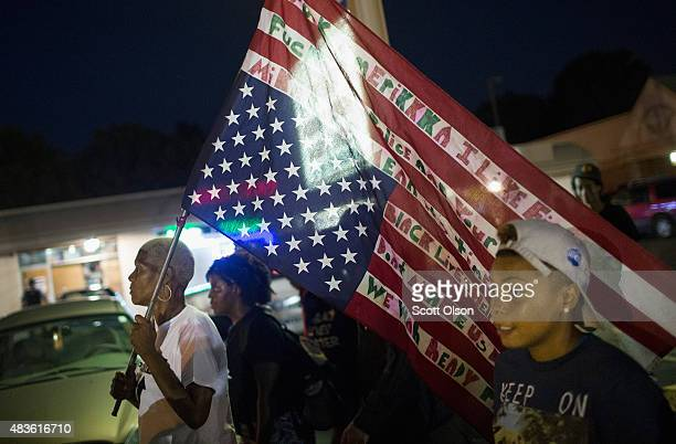Demonstrators marking the oneyear anniversary of the shooting of Michael Brown protest along West Florrisant Street on August 10 2015 in Ferguson...
