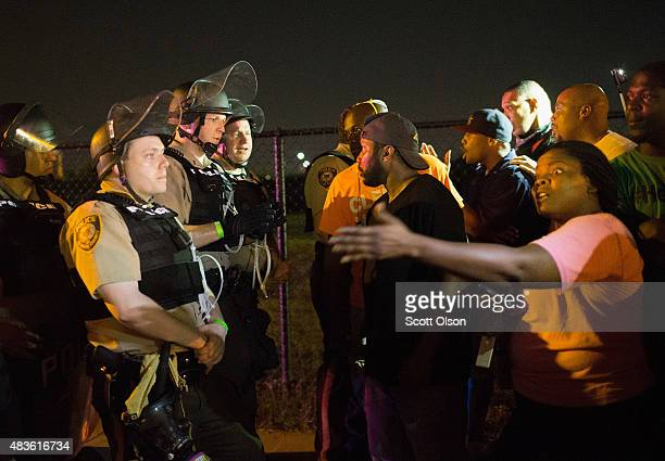 Demonstrators, marking the one-year anniversary of the shooting of Michael Brown, confront police during a protest along West Florrisant Street on...