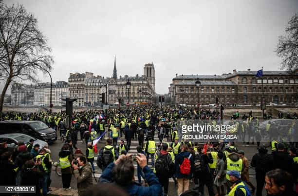 Demonstrators of the French 'yellow vests' movement gather near the ile de la Cité in central Paris on December 22 2018 during a protest as the...