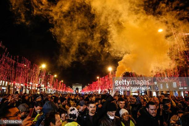 TOPSHOT Demonstrators of the French 'yellow vests' movement gather on the Champs Elysees avenue at the end of a protest in Paris on December 22 2018...