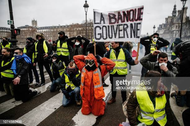 TOPSHOT Demonstrators of the French 'yellow vests' movement kneel down as they face police during a protest in central Paris on December 22 2018 as...