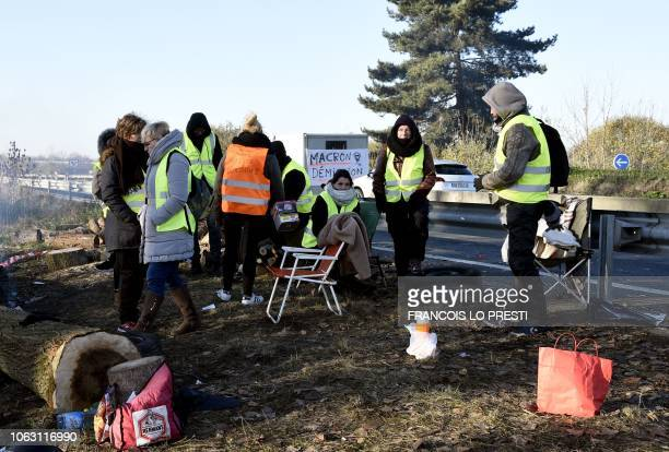 Demonstrators of the Yellow Vests movement stand by a fire on November 18 2018 at the border point with Belgium in Crespin near Valenciennes northern...
